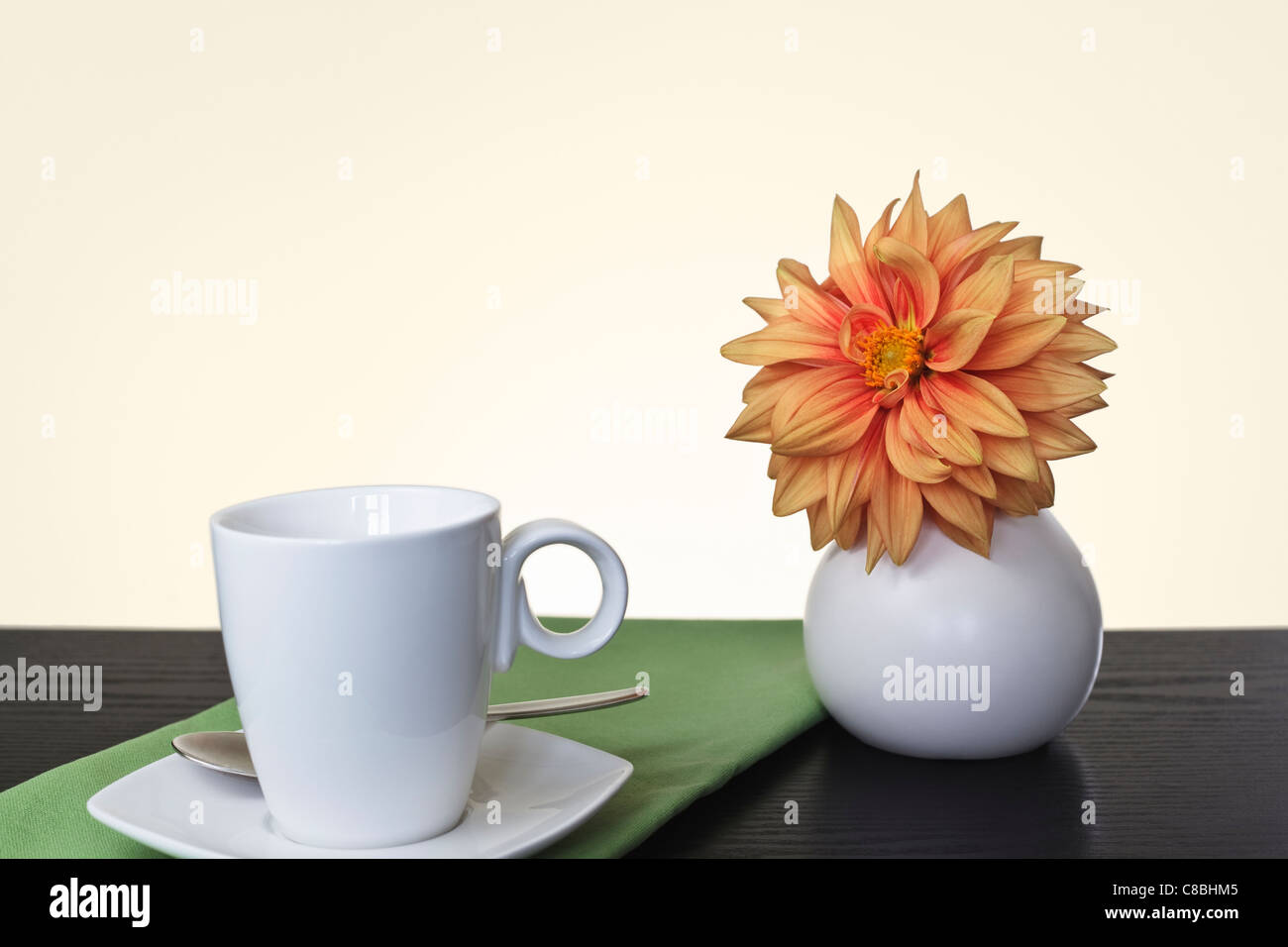 Dahlia in white round Vase with white cup and saucer - Stock Image