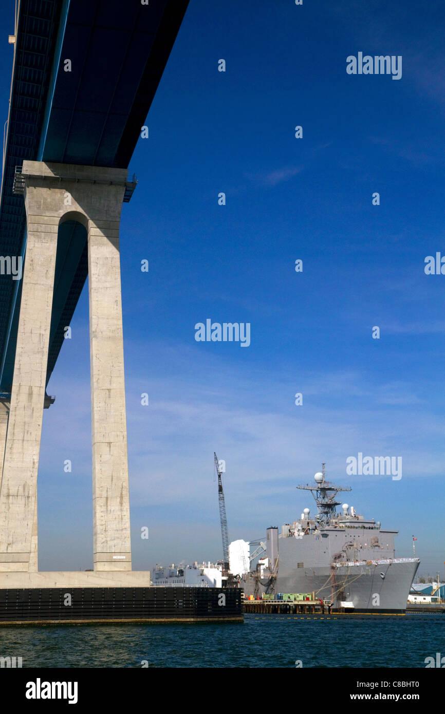 Navy ship under the Coronado Bridge in San Diego, California, USA. - Stock Image