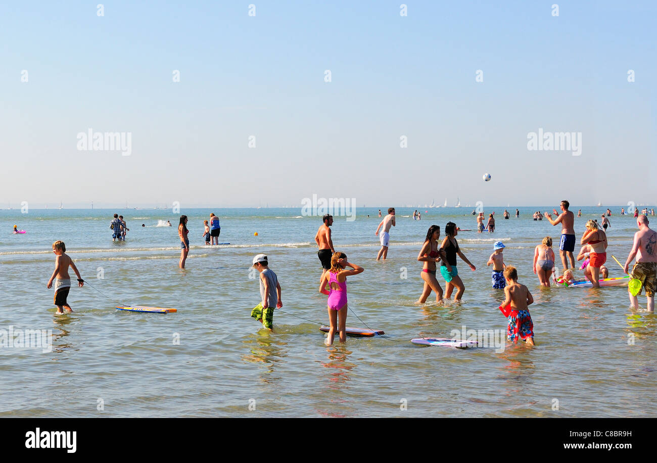 Crowds cooling off in the water and enjoying the unusually hot October weekends sunshine   at West Wittering beach - Stock Image