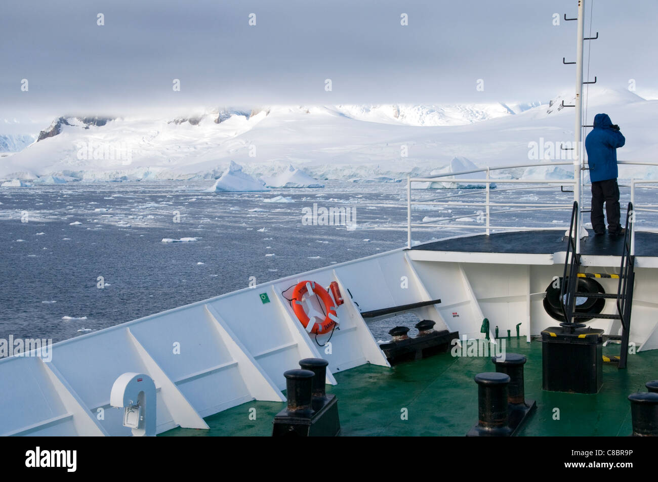 A male tourist standing on the deck of Antarctic expedition vessel the MV Ushuaia - Stock Image