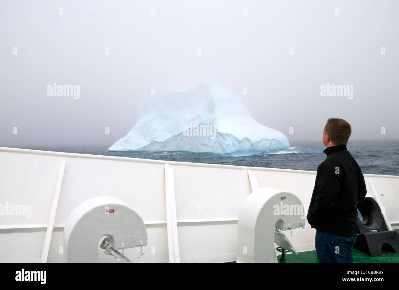A male tourist standing on the deck of Antarctic expedition vessel the MV Ushuaia looking at an iceberg in the Southern - Stock Image