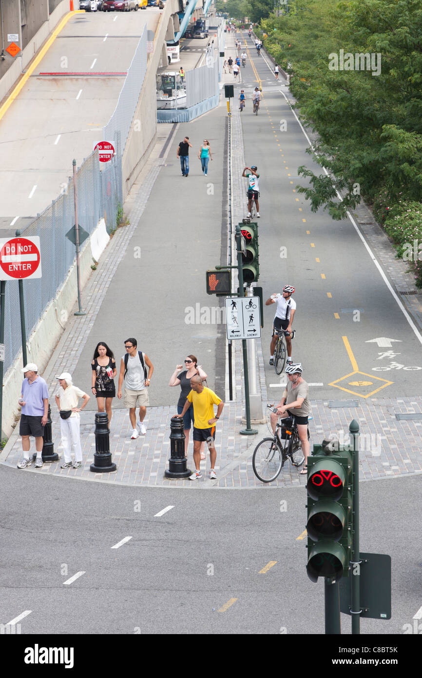 Cyclists, runners, and pedestrians utilize the paths and bike lanes on a section of the Hudson River Greenway north - Stock Image