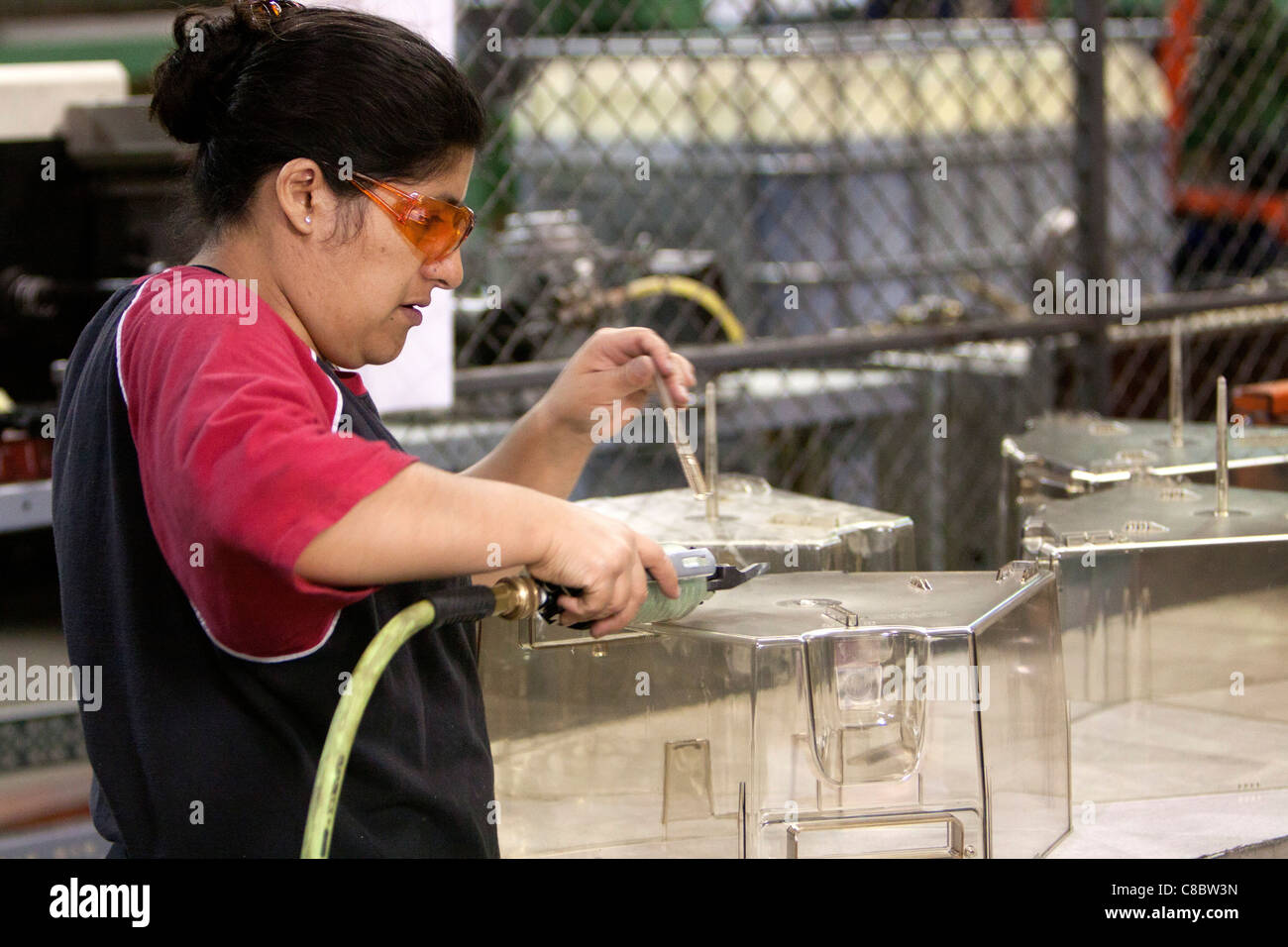 A woman finished a plastic product at a plastiA woman finished a plastic product at a plastic injectioc injection - Stock Image