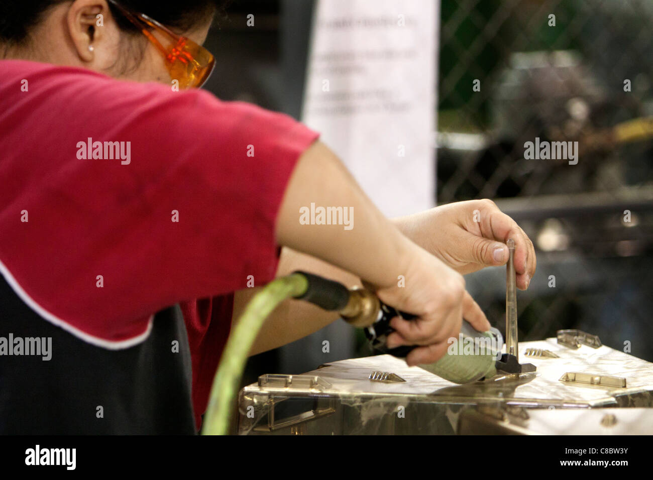 A woman finished a plastic product at a plastic injection molding plant. - Stock Image