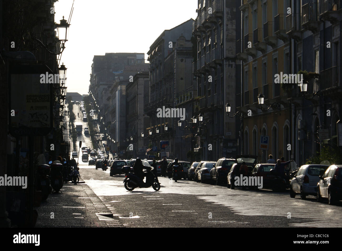 Steep street (Via Antonino di Sangiuliano) built with black Etna's magma in Catania on Sicily during late afternoon - Stock Image