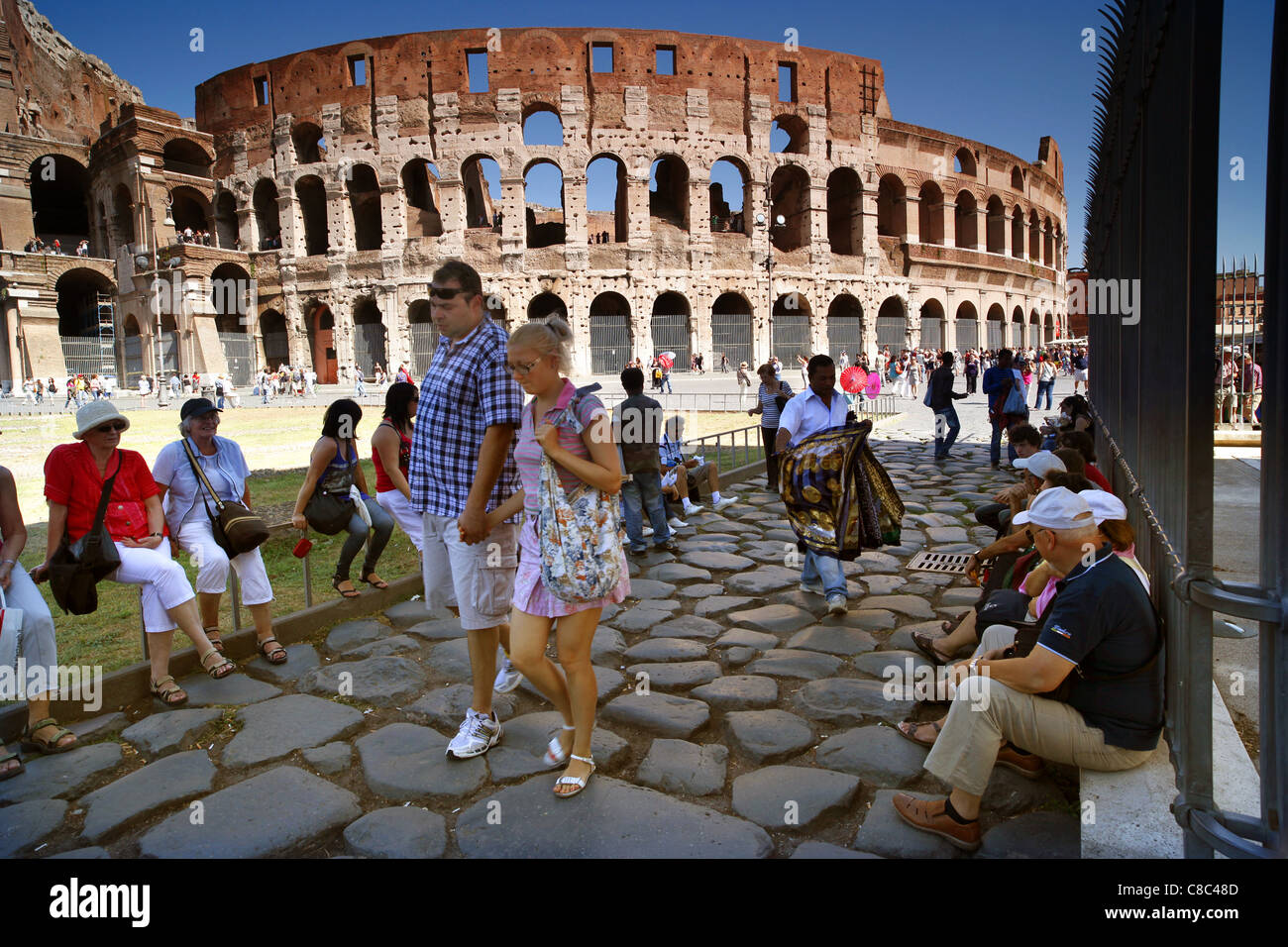 Tourists outside the Colosseum in Rome, Italy. - Stock Image