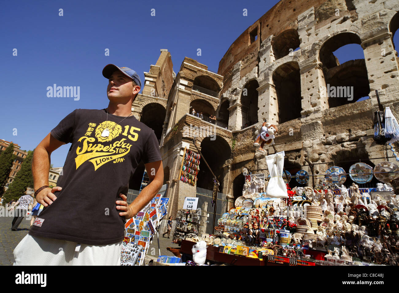 A souvenir stallholder waits for tourists outside the Colosseum in Rome, Italy. - Stock Image