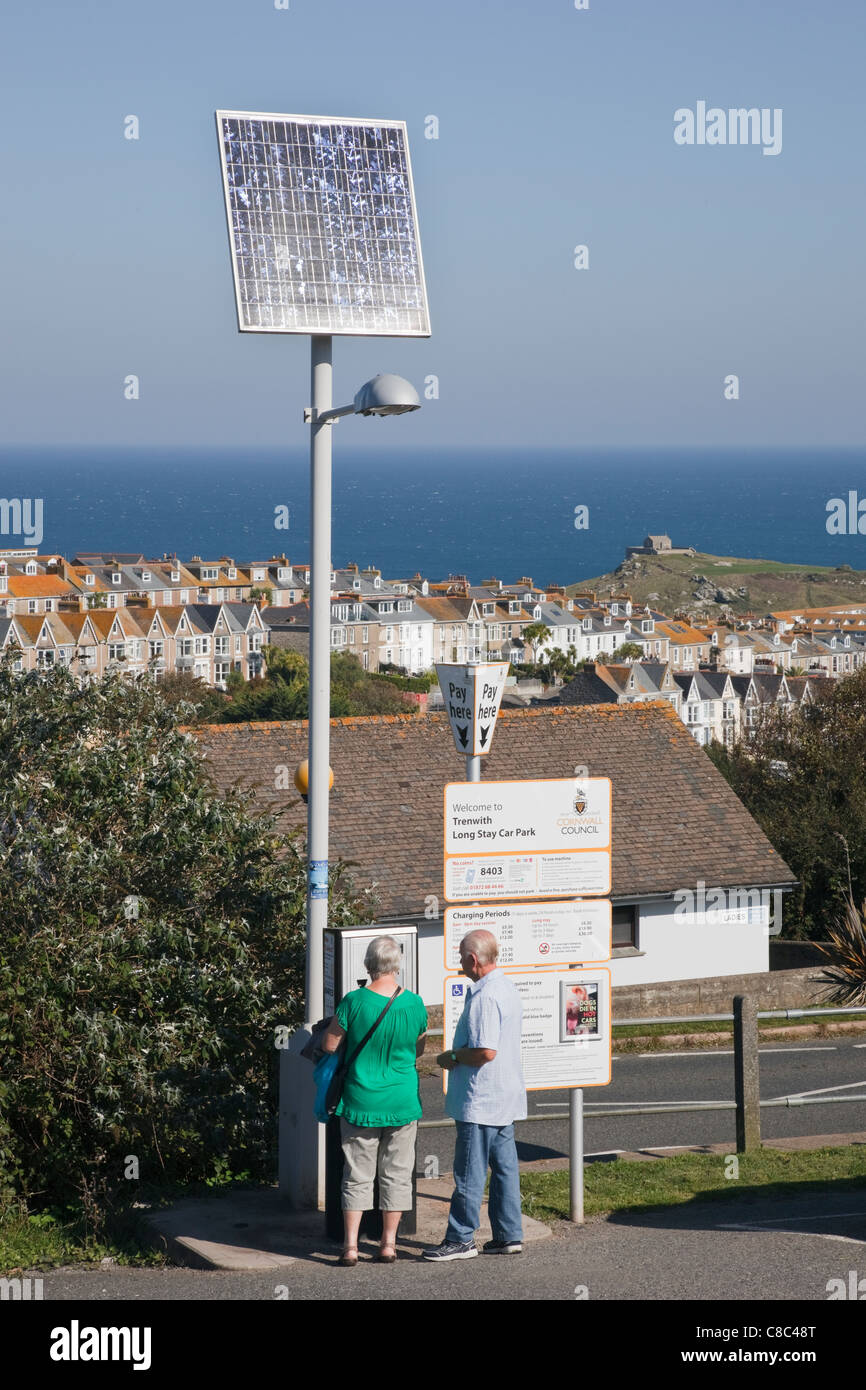 People buying parking ticket from a solar powered machine in expensive Trenwith car park. St Ives Cornwall England - Stock Image