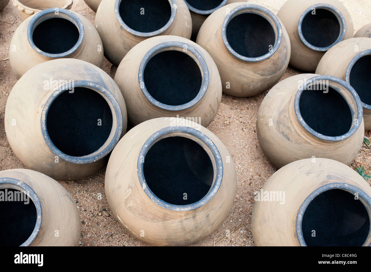 Hand made indian water pots drying in the sun before firing. Andhra Pradesh, India - Stock Image
