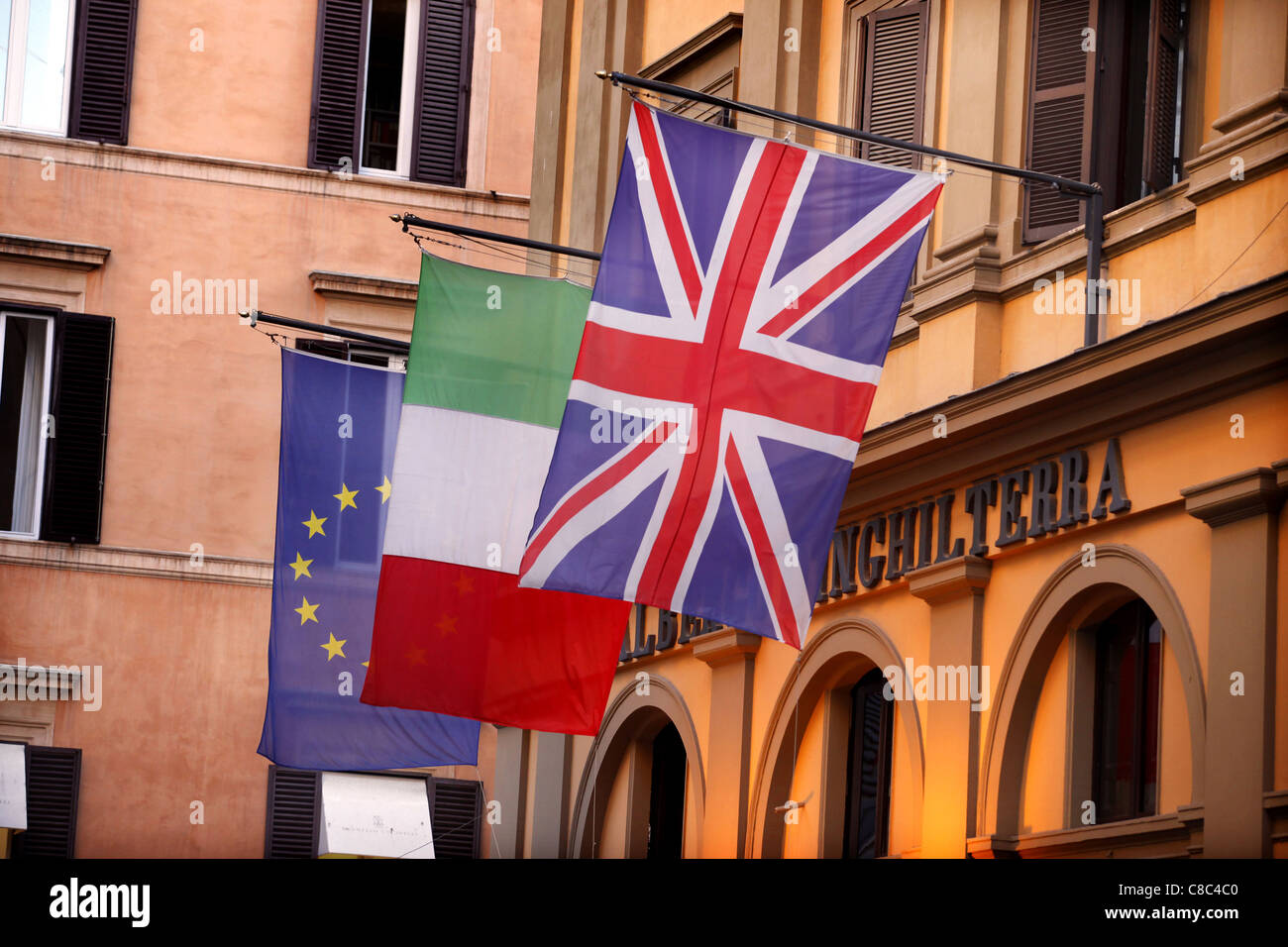 European, Italian and Union flags fly outside the Albergo Inghilterra in Rome, Italy. - Stock Image