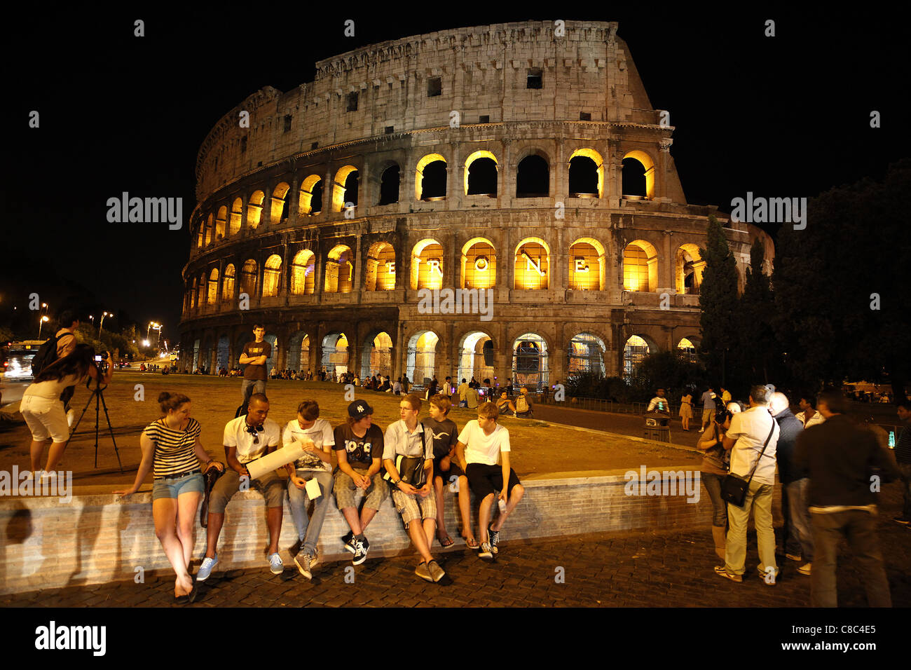 Tourists outside the Colosseum in Rome, Italy at night. - Stock Image