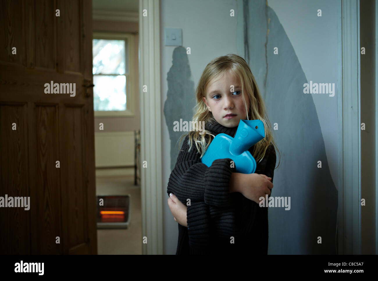 A  young girl holding a hot water bottle and wearing a large jumper in a run down flat with a electric fire in back - Stock Image