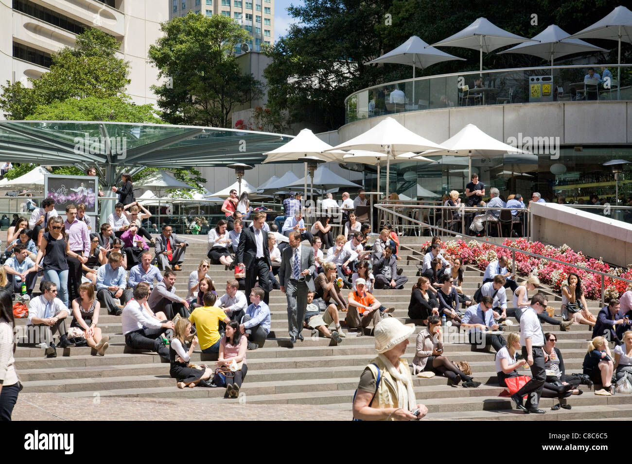 office workers sitting outside in sydney enjoying the summer weather - Stock Image