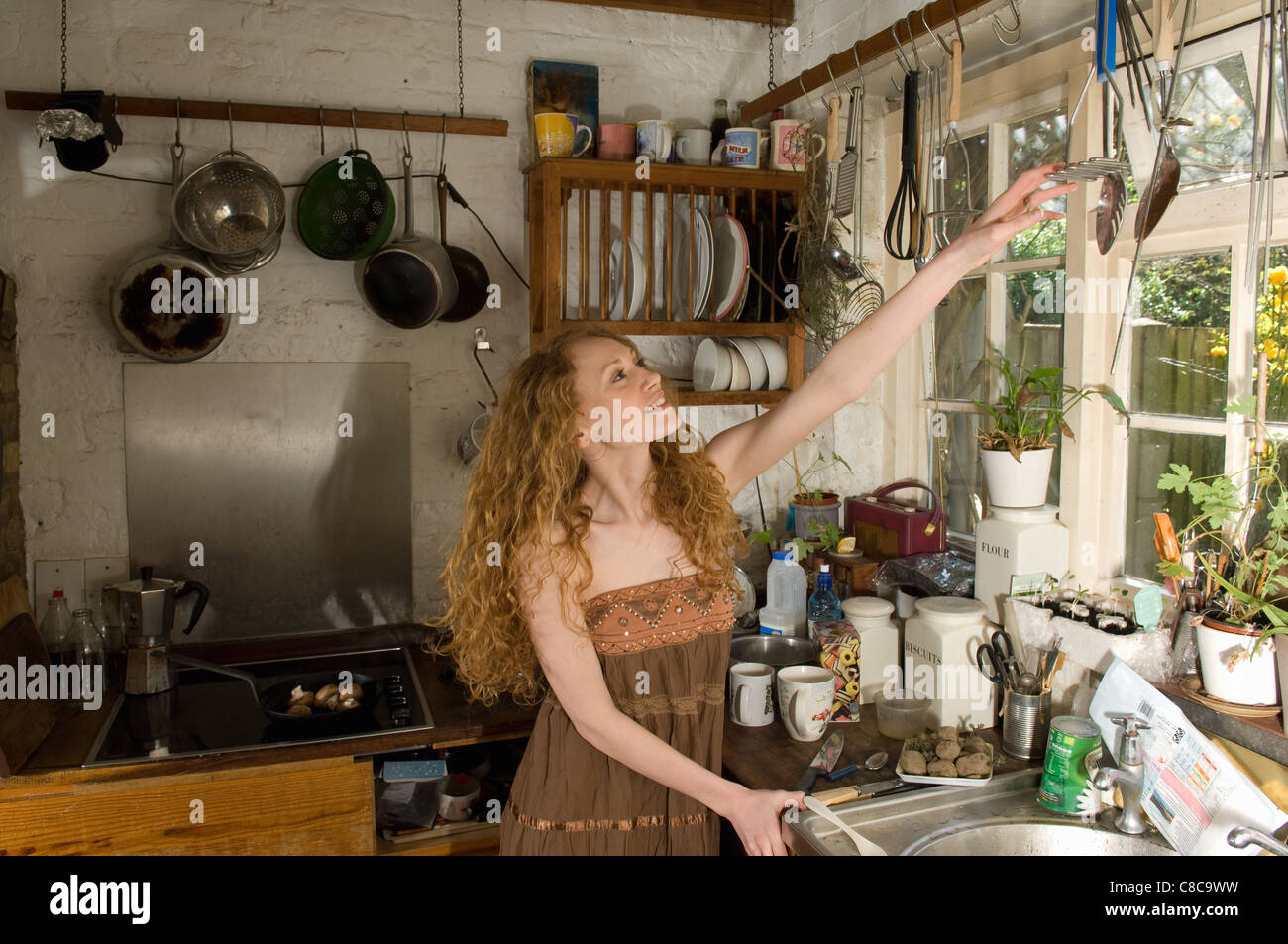 Woman selecting utensil in kitchen - Stock Image