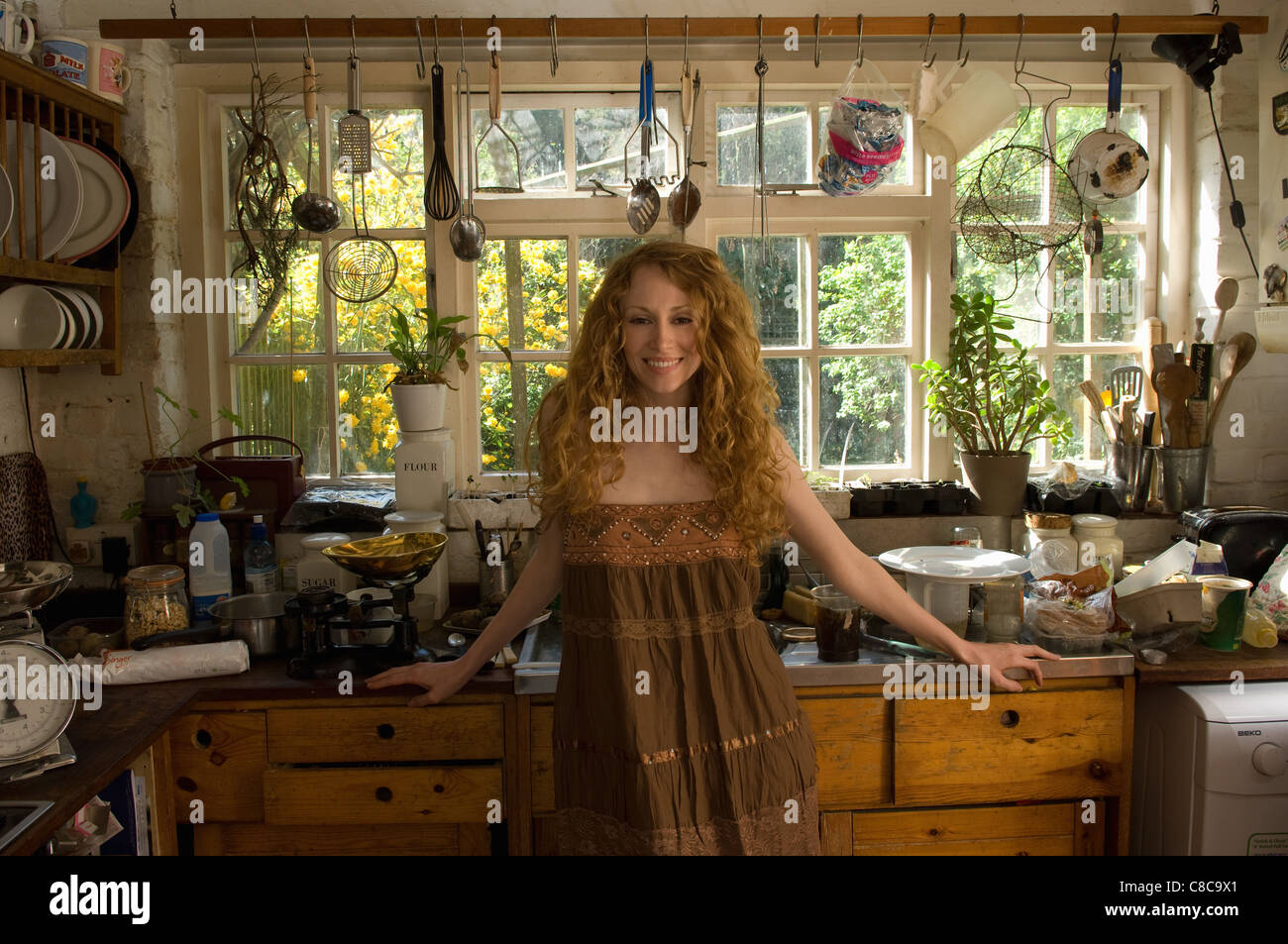 Woman standing in kitchen - Stock Image