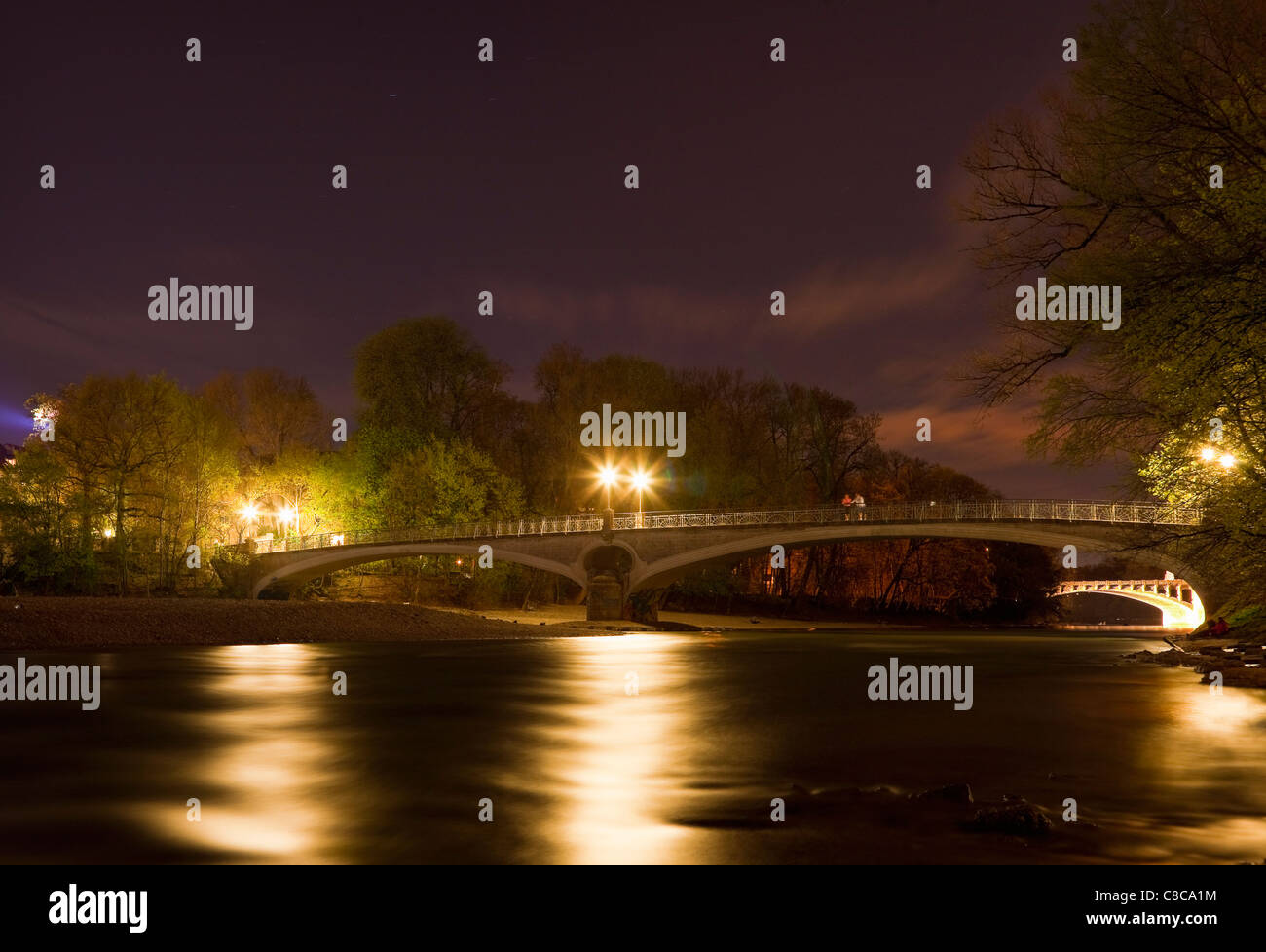 Lit bridge over river at night - Stock Image