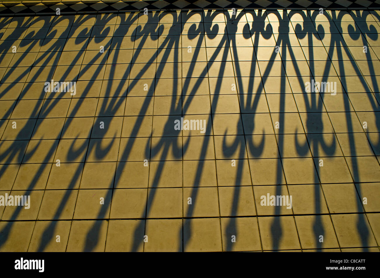 Shadows of the ornate iron railings of a Victorian bandstand in early morning light - Stock Image