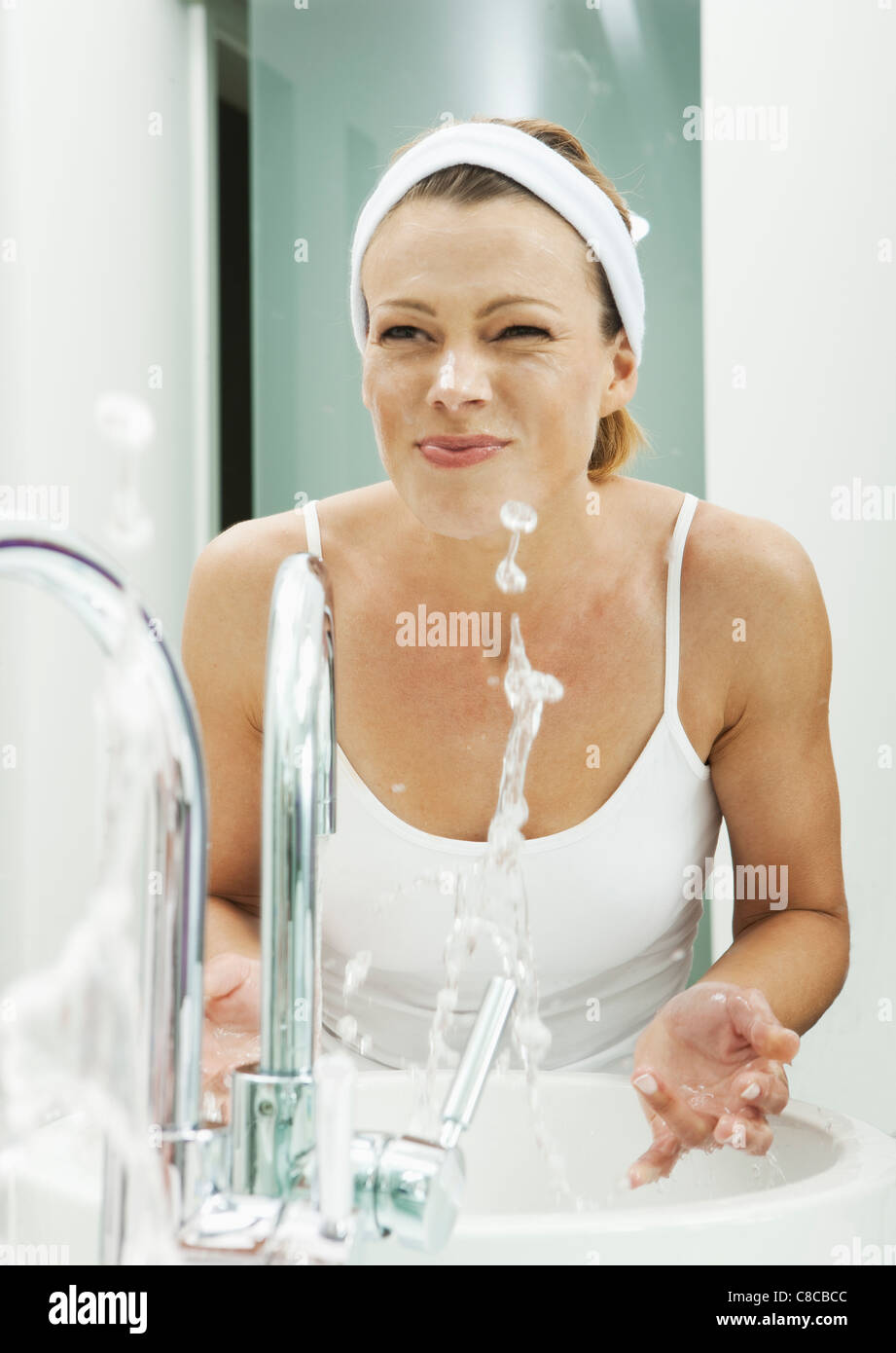 Woman washing her face in bathroom - Stock Image