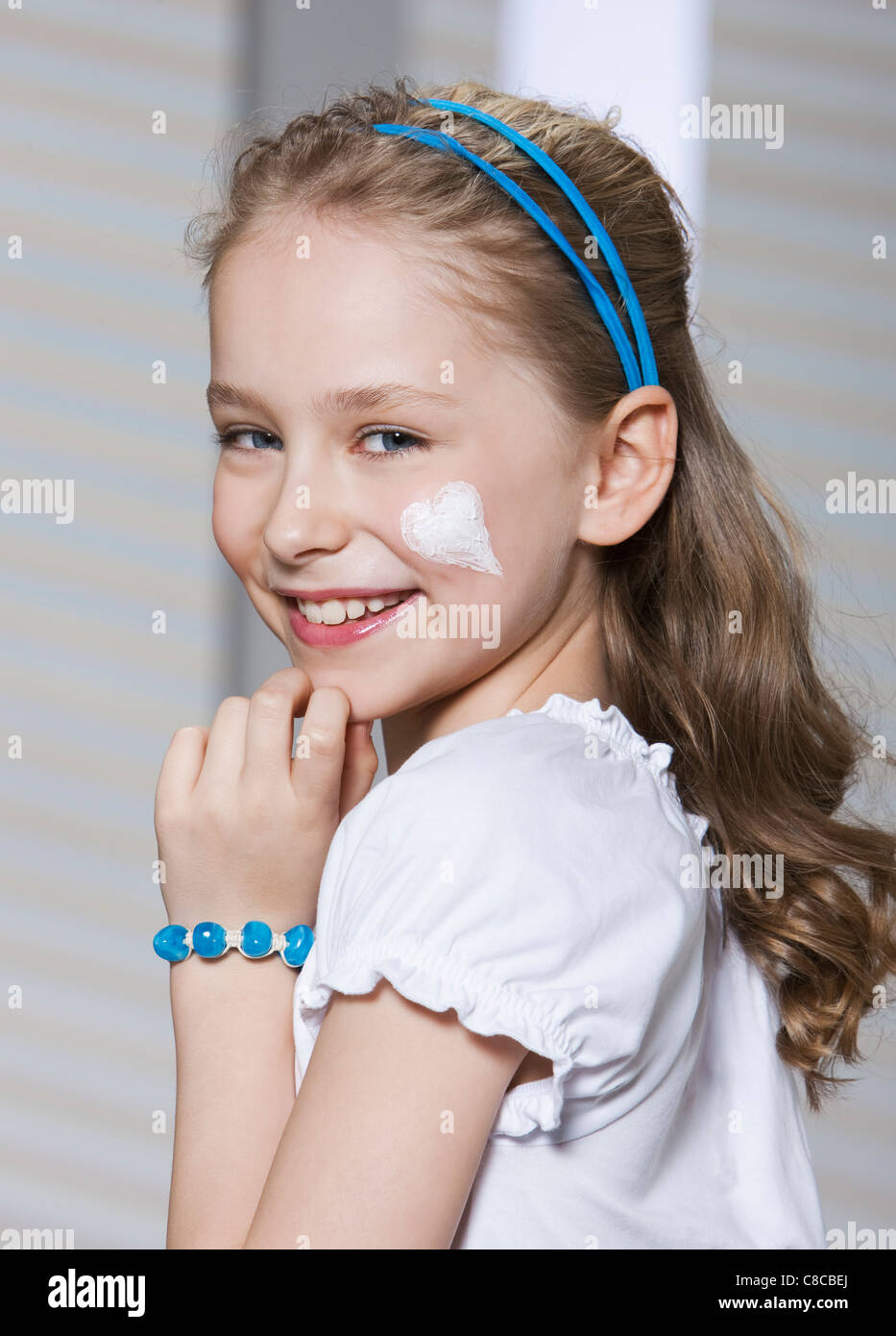 Girl with heart-shaped moisturizer - Stock Image