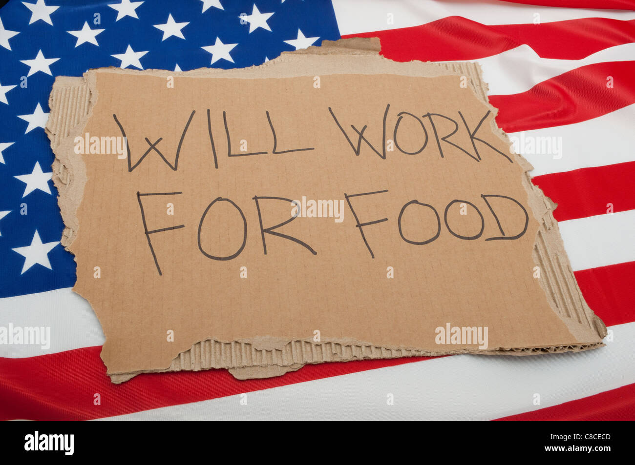Unemployment in USA - Sign Will Work For Food on Cardboard on American Flag - Stock Image