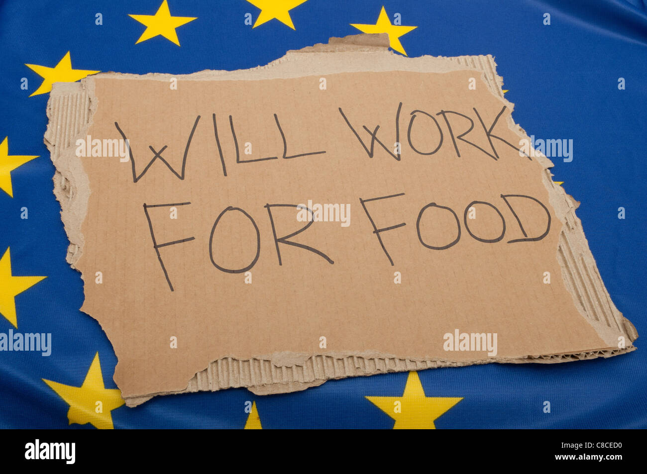 Unemployment in EU - Sign Will Work For Food on Cardboard on European Union Flag - Stock Image