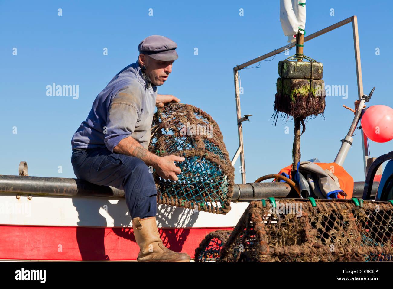 Fisherman taking crab pots off his fishing boat Cromer Norfolk East Anglia England UK GB EU Europe - Stock Image
