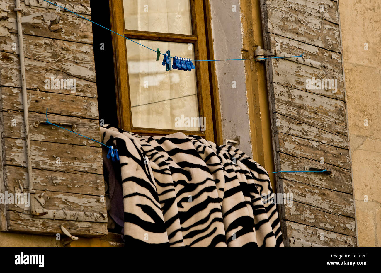 Bedding airs on a balcony of apartment in the middle of Arles, Camargue,  France - Stock Image