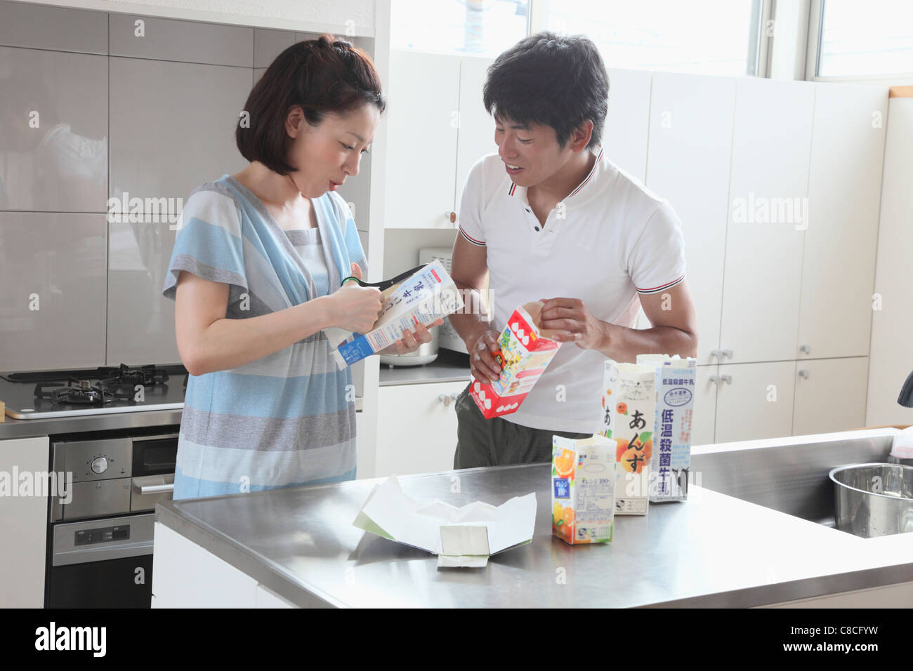 Mid adult couple opening milk carton for recycle - Stock Image
