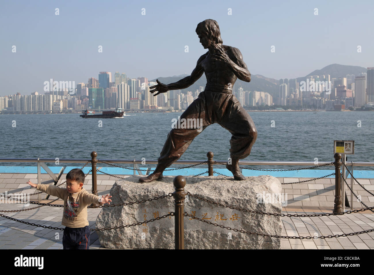A child poses in front of the statue of Hong Kong martial arts and film star Bruce Lee (1940-73) on the Avenue of - Stock Image