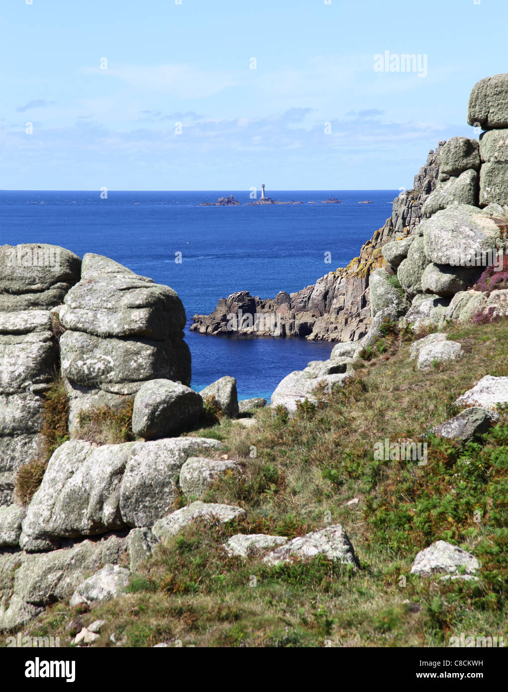 Longships lighthouse off Land's End Cornwall England UK viewed through rocks on the South West Coastal path - Stock Image
