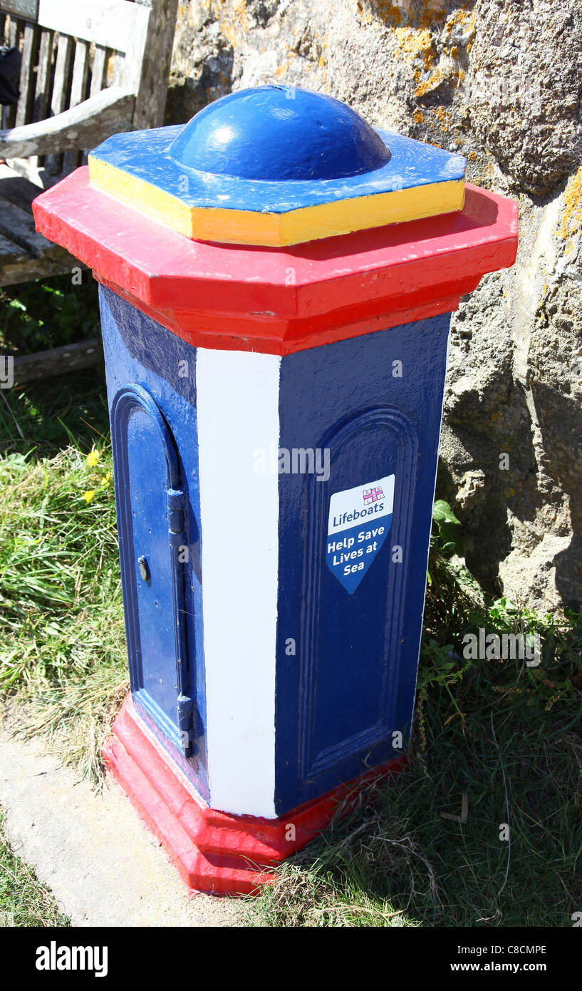 A colourful Royal national lifeboat Institute money box or pillar for donations - Stock Image