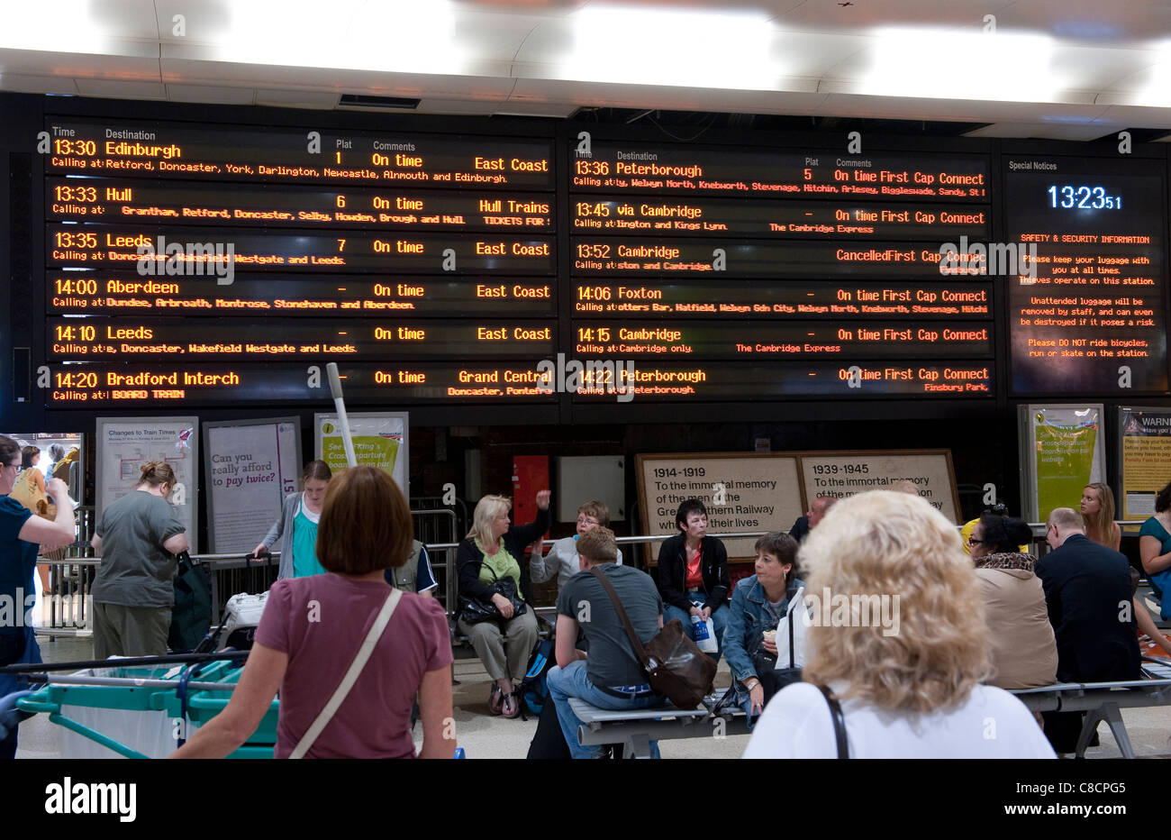 Passengers looking at a passenger information board at Kings Cross railway Station in London. - Stock Image