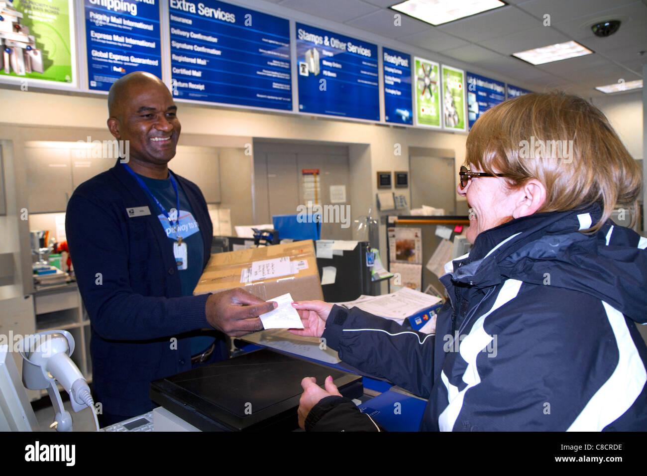 Female customer and male african american postal worker in Boise, Idaho, USA. - Stock Image