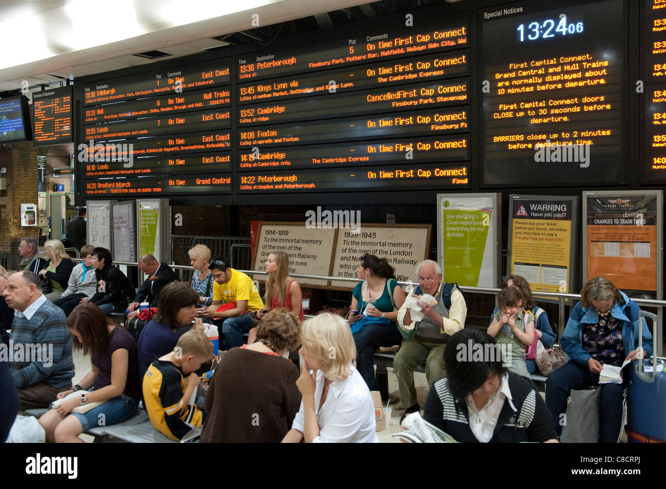 Passengers waiting beneath a passenger information board at Kings Cross railway Station in London. - Stock Image