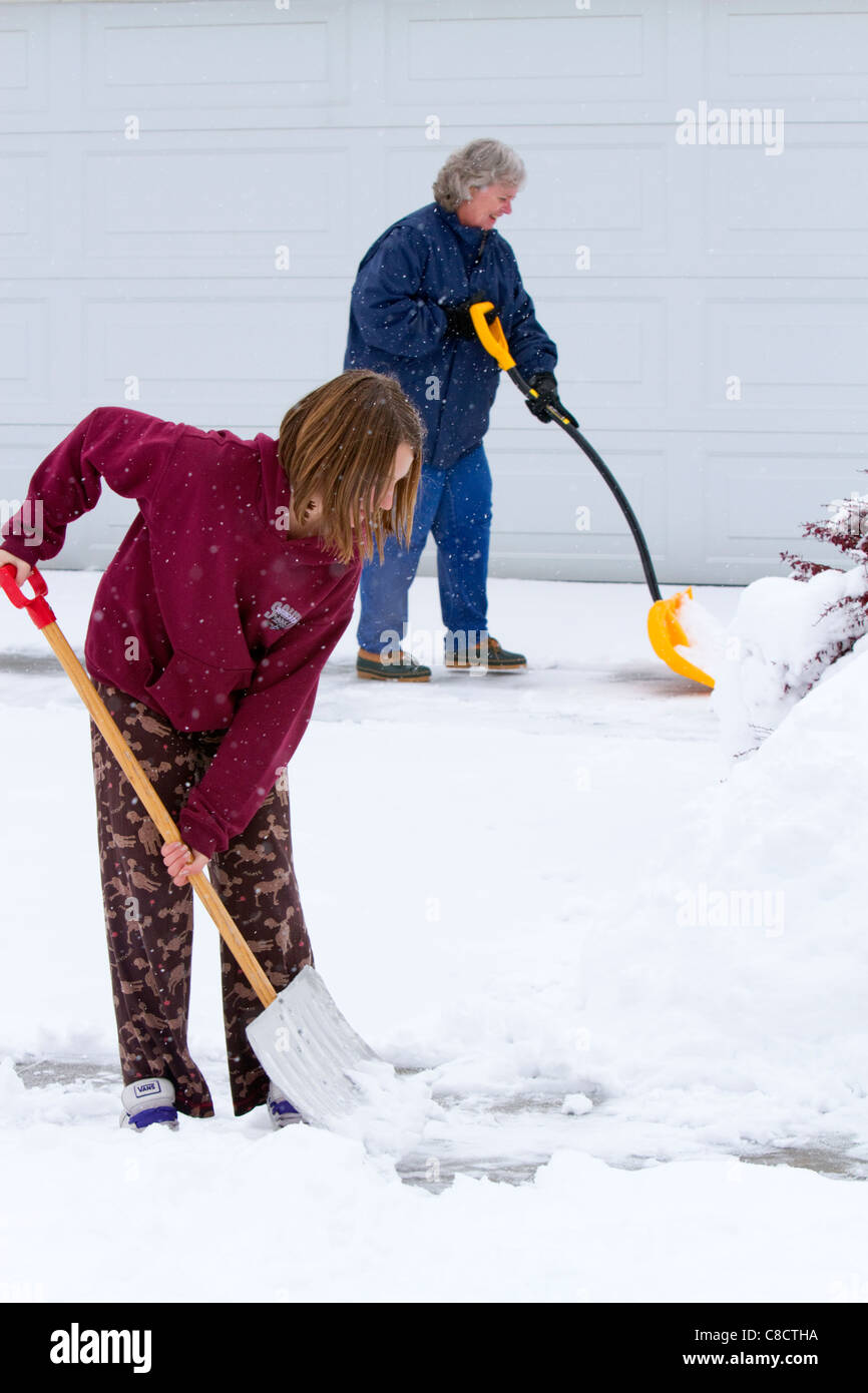 People shovel winter snow off of a driveway in Boise, Idaho, USA. - Stock Image