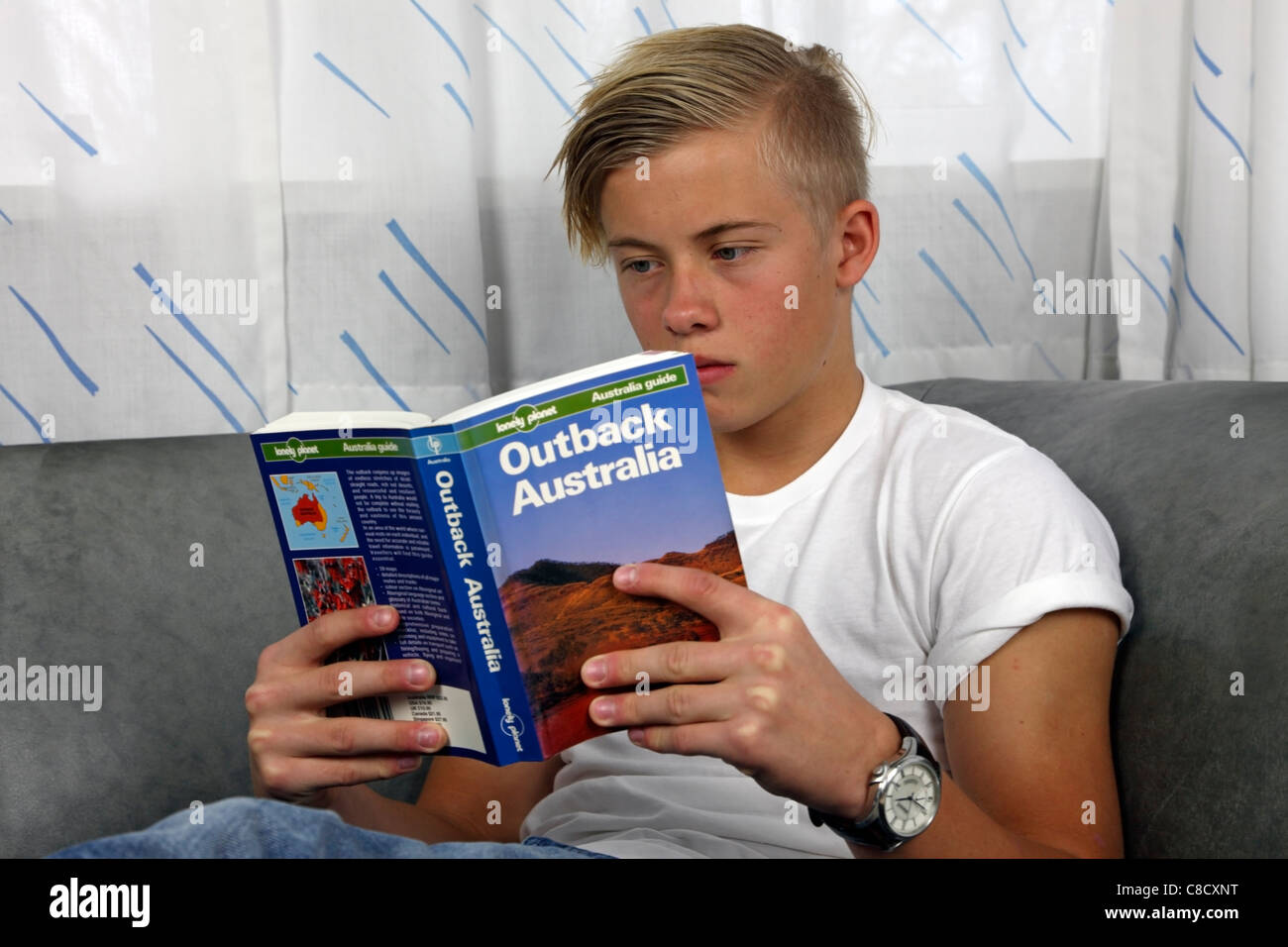 Relaxed, male, Danish teenager reading Lonely Planet Outback Australia in preparation of a holiday in the wilderness - Stock Image