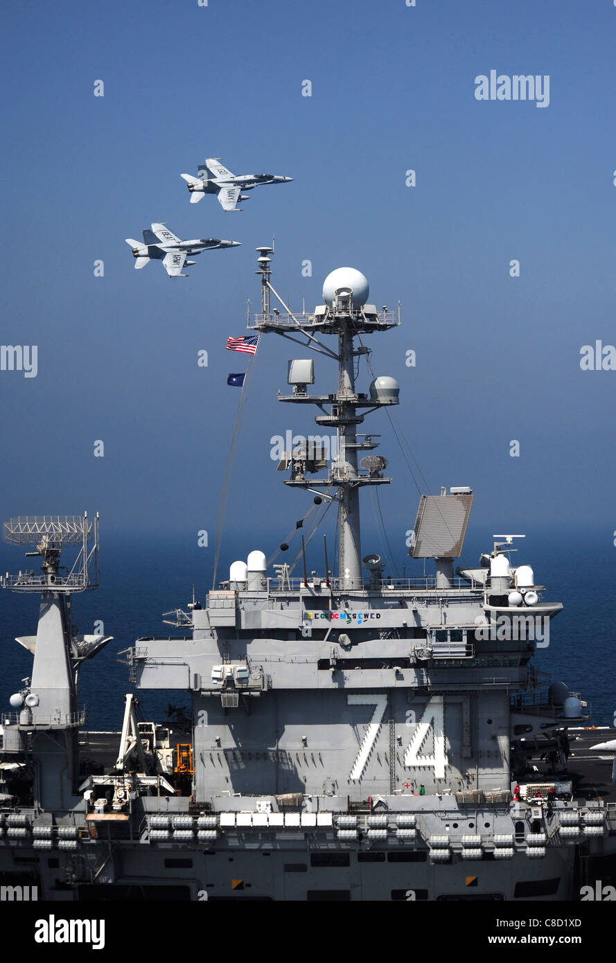 F/A-18C Hornets assigned to the Golden Dragons of Strike Fighter Squadron (VFA) 192 fly over the aircraft carrier - Stock Image