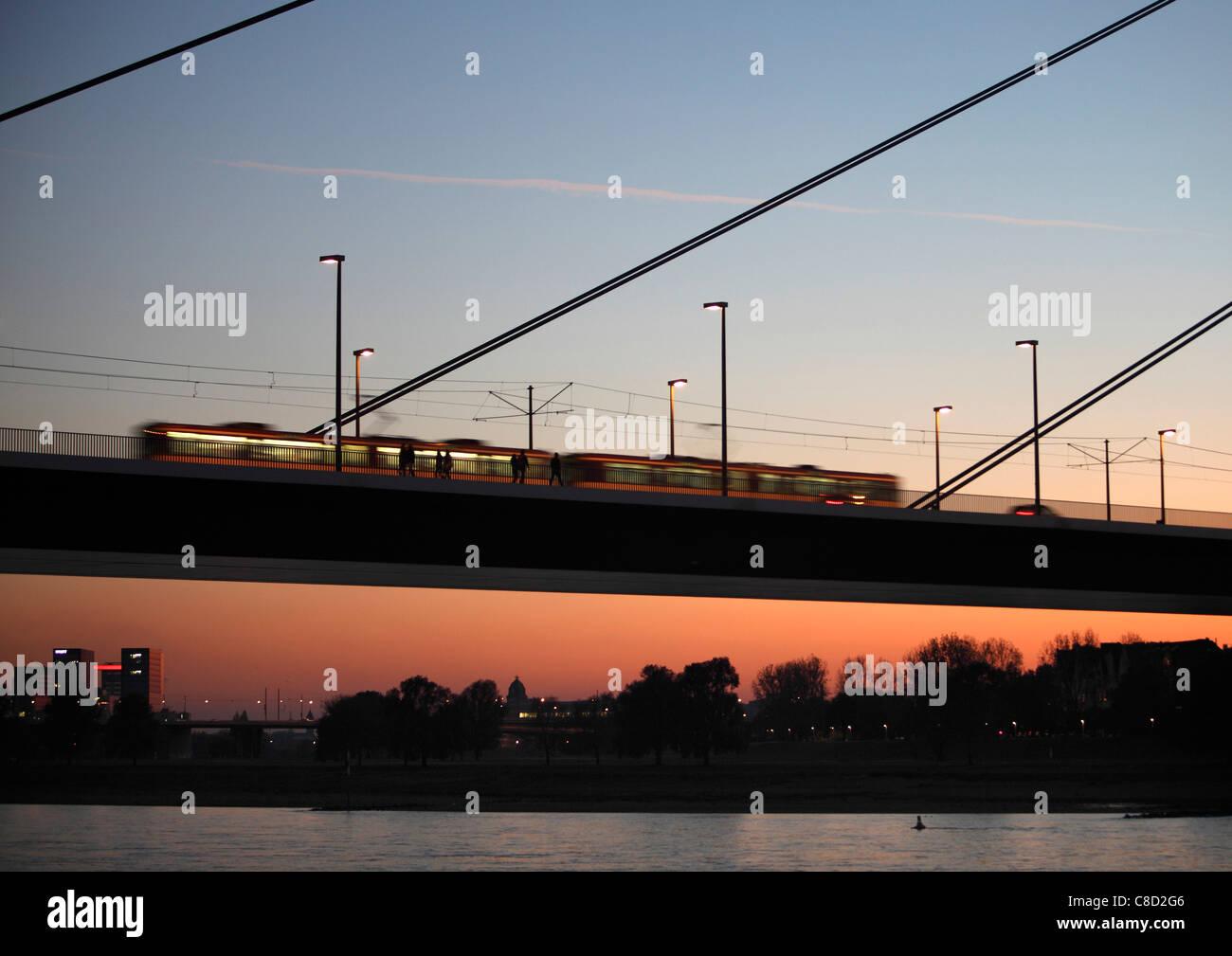 Rheinkniebrücke, a long bridge over river Rhine, Düsseldorf, Germany. For pedestrians, cars, bikes, tram, - Stock Image