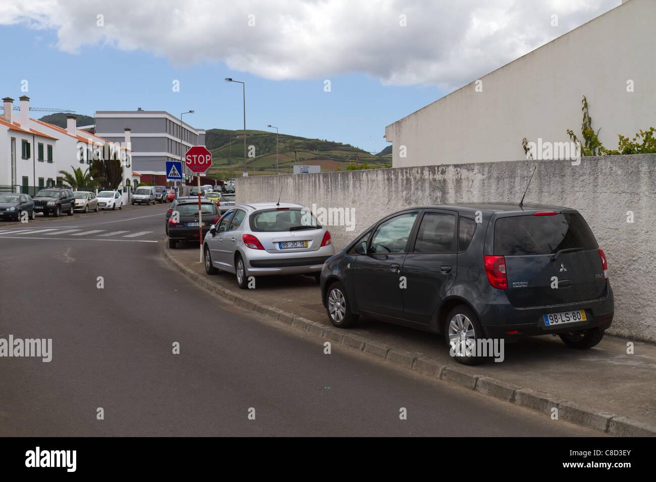 Cars parked on the sidewalk  Ribeira Grande, São Miguel island, Azores. - Stock Image