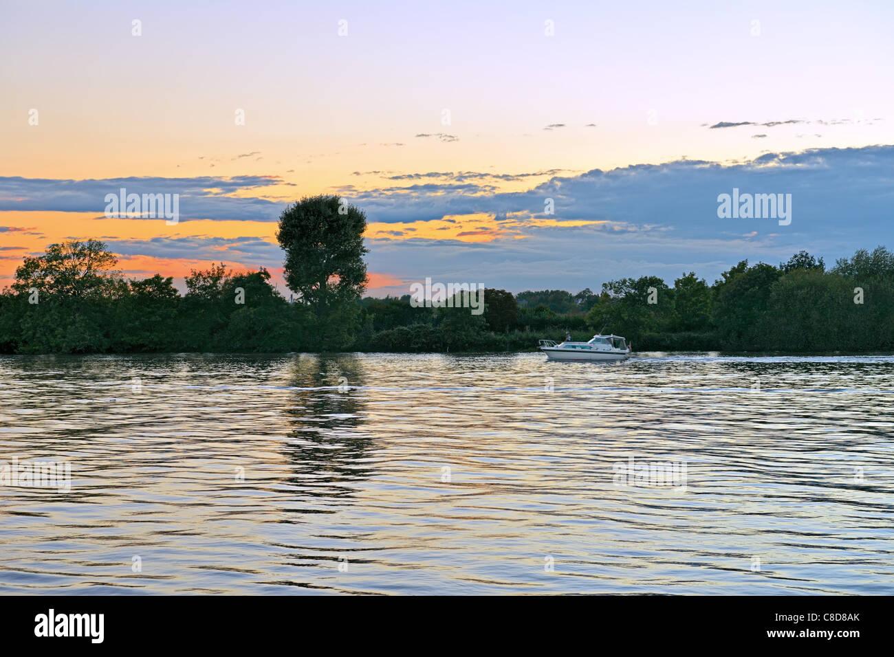 Boat cruising on River Thames, Hammersmith, London, at sunset - Stock Image