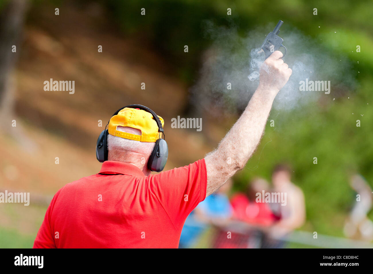 A referee fires the starter pistol for the runners of a track race. - Stock Image
