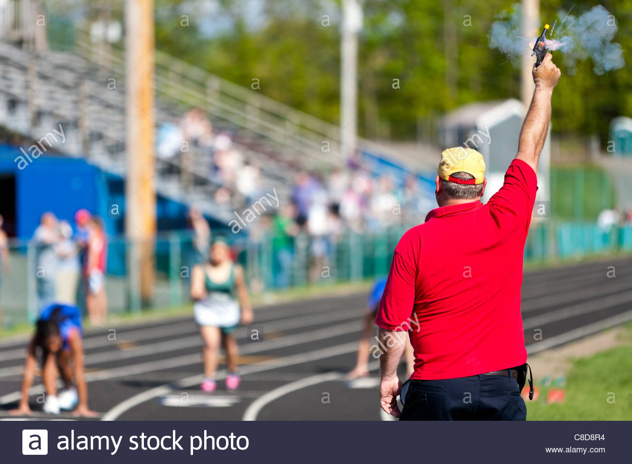 A referee fires the starter pistol for the runners of a track race