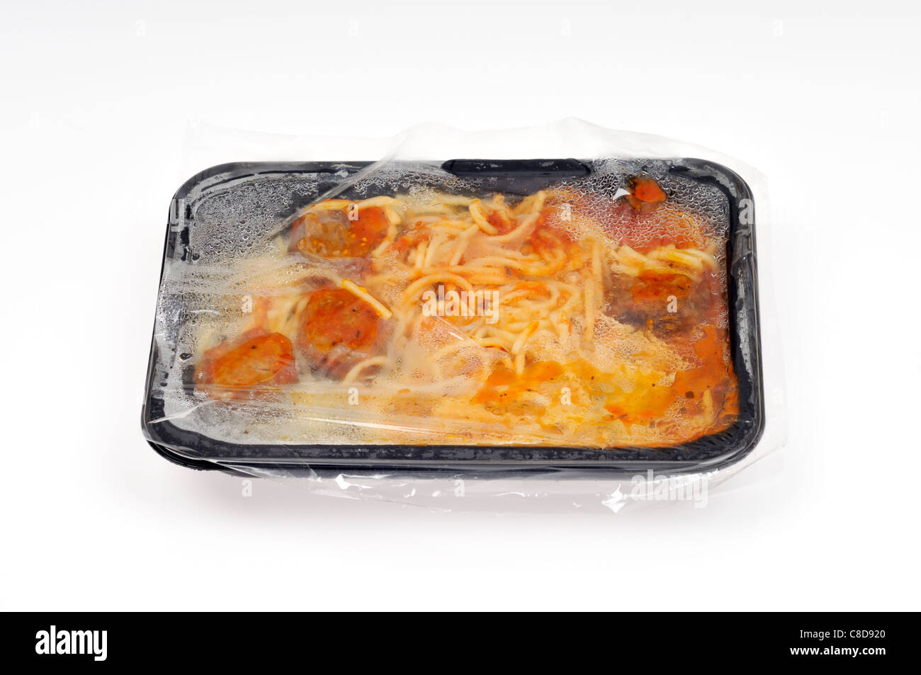 Tray of hot cooked microwave spaghetti and meatballs ready meal with plastic tray & film cover on white background - Stock Image