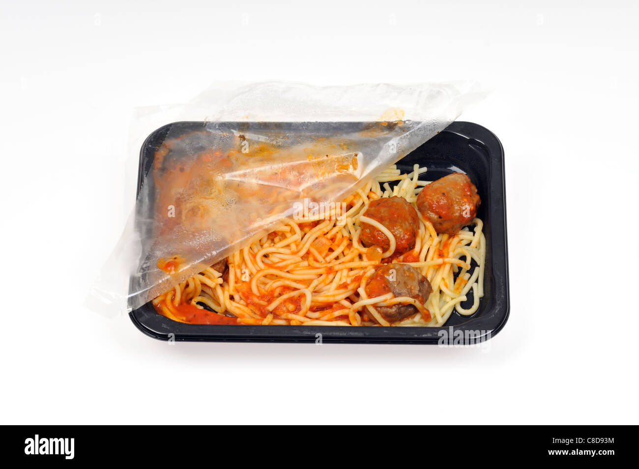 Tray of microwave spaghetti and meatballs with plastic cover still on & pulled open fresh out of cooking in - Stock Image