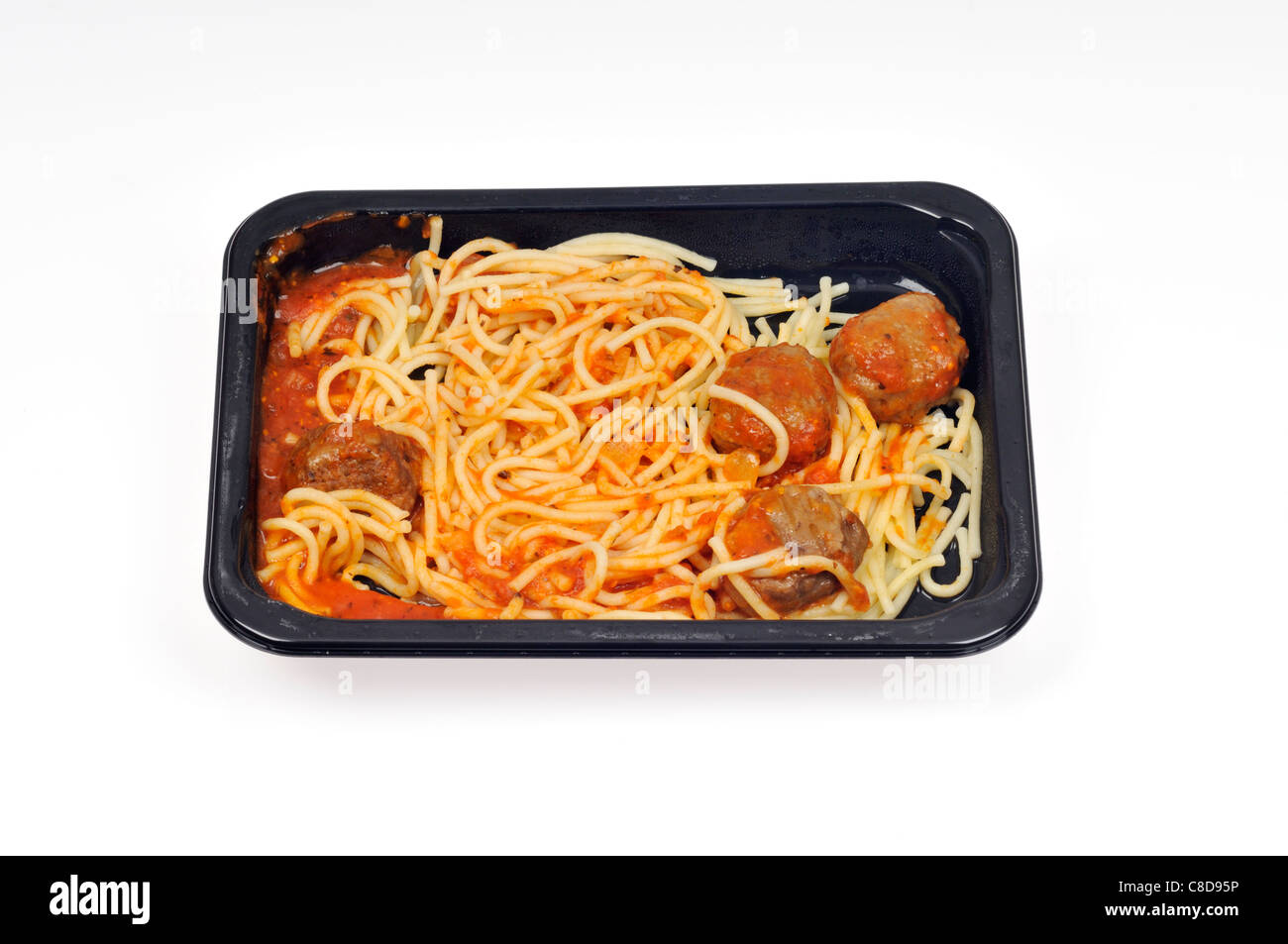Tray of microwave cooked spaghetti and meatballs readymeal on white background, cutout. - Stock Image