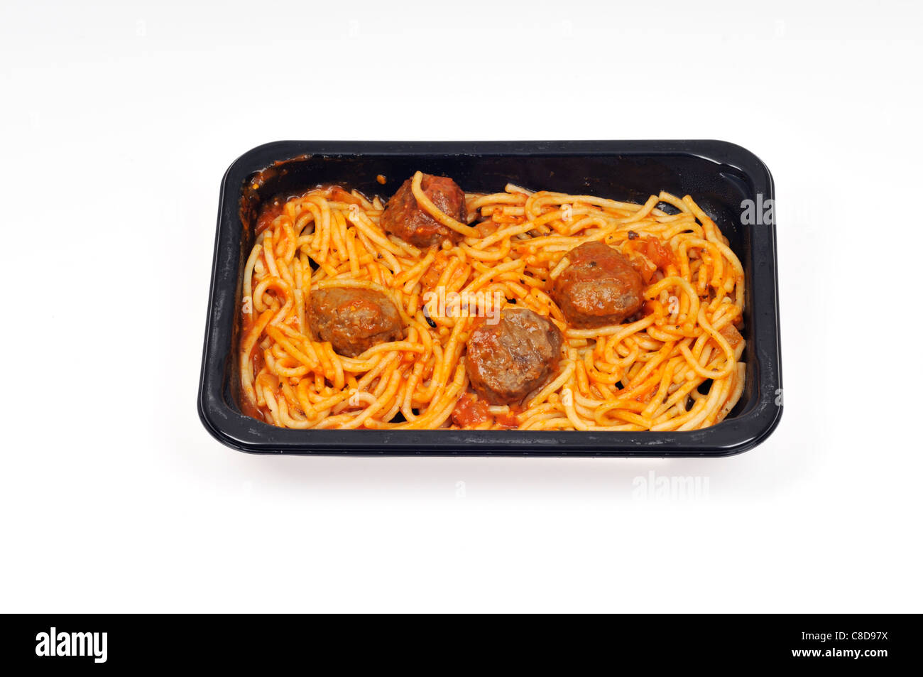 Tray of cooked microwave spaghetti and meatballs readymeal on white background, cutout. - Stock Image