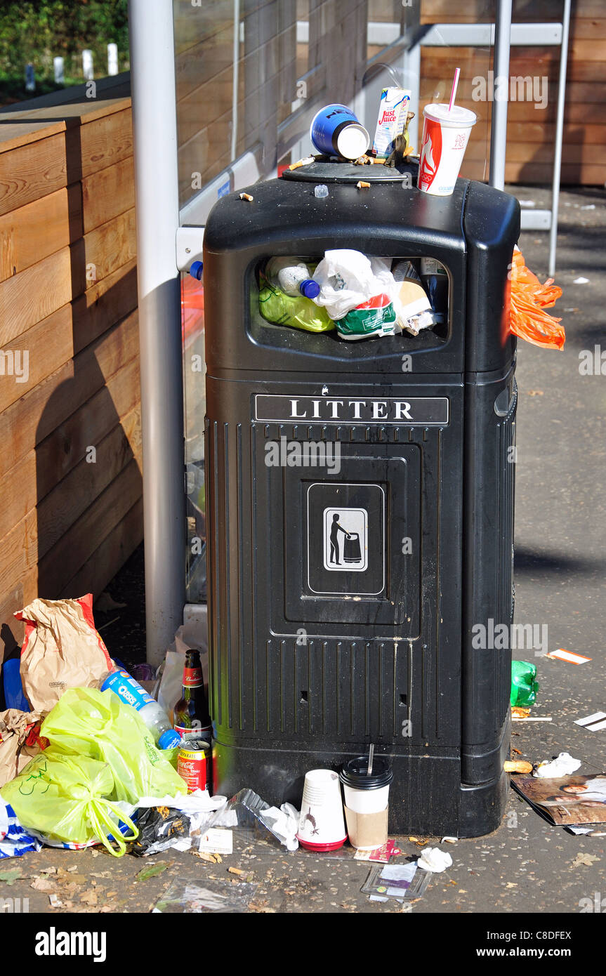 Overflowing rubbish bin outside Railway Station, Barnes, London Borough of Richmond upon Thames, London, England, - Stock Image