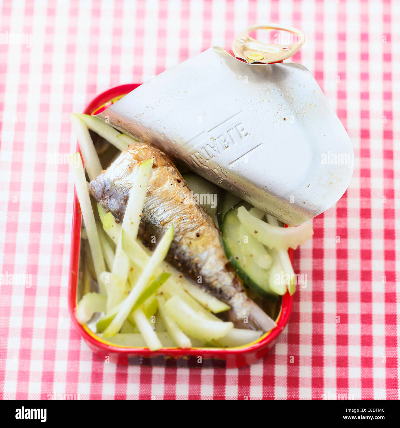 Canned sardine ,apple,celery and cucumber salad served in it's tin - Stock Image