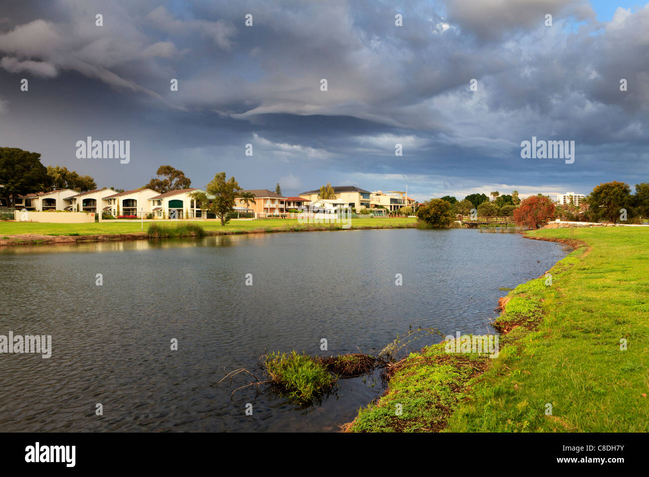 Large lakeside houses beneath a stunning stormy sky in affluent South Perth, Western Australia. - Stock Image