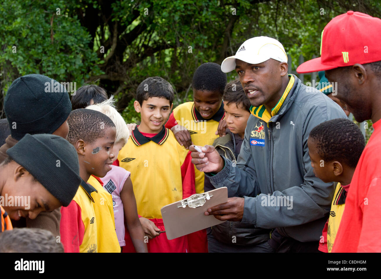 Coach intructs his youth team during half time Rygersdal Football club Cape Town South Africa - Stock Image